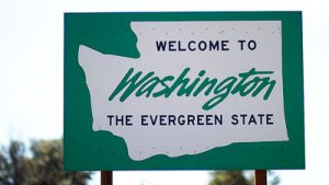 A green road sign with a white image of the state of Washington with the text: Welcome to Washington The Evergreen State.