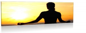 A sitting person with their arms in a meditation post silhouetted against a setting sun.