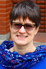 A smiling woman in sunglasses.