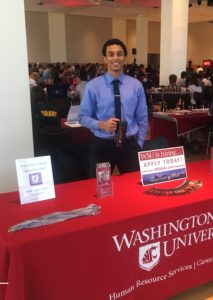 A man in a blue shirt and tie standing behind a WSU career fair table.