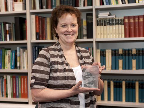 A smiling woman holding a glass award standing in front of a tall bookshelf filled with books.