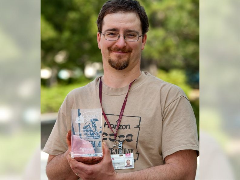 A smiling man holding a glass award with green trees in the background.