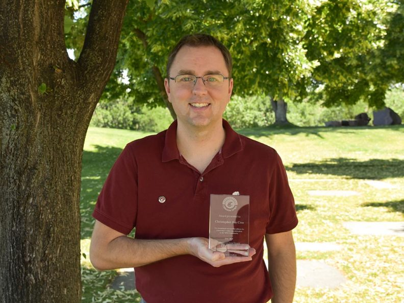 A smiling man in a red shirt holding a glass award, standing outside next to a tree.