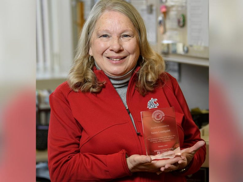 A smiling woman wearing a red shirt and holding a glass award.