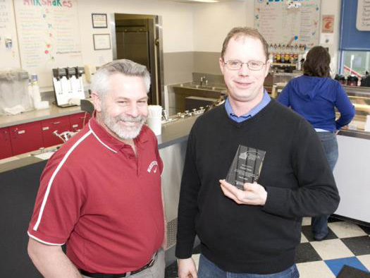Two smiling men, one holding a glass award, standing in front of an ice cream counter.