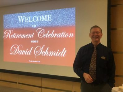 A smiling man standing in front of a screen with the text: Welcome to the Retirement Celebration in honor of David Schmidt.