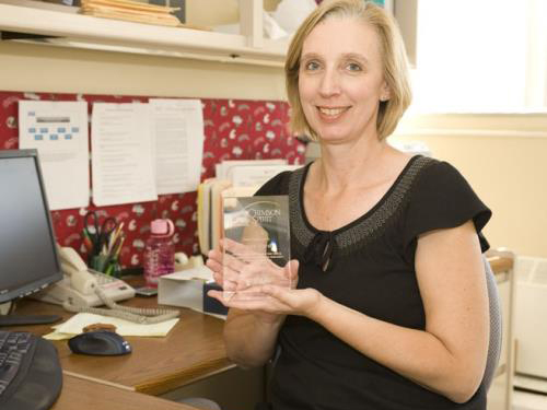 A smiling woman seated at a computer desk holding a glass award.