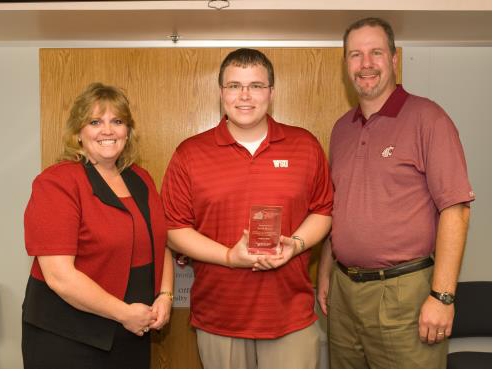 A smiling man in a red WSU shirt holding a glass award flanked by a smiling woman and man.