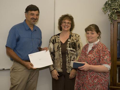 Three smiling people, one holding a blue box and another a certificate.