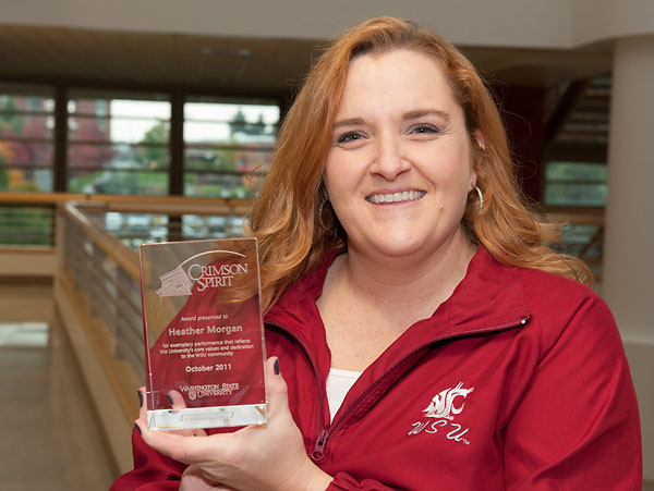 A smiling woman in a red Cougars jacket holding a glass award.