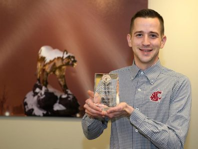 A smiling man holding a glass award with a large photo of a Cougar statue in the background.