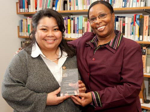 Two smiling women, one holding a glass award. A large bookcase in the background.