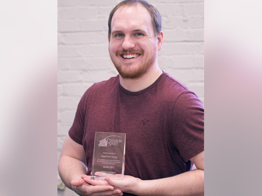 A smiling man holding a glass award.