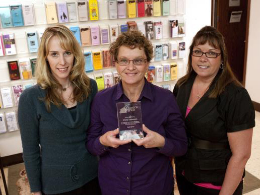 A smiling woman holding a glass award, flanked by two other women.