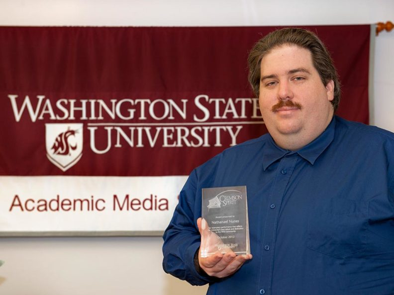 A smiling man holding a glass award in front of a red and white banner that reads: Washington State University Academic Media.