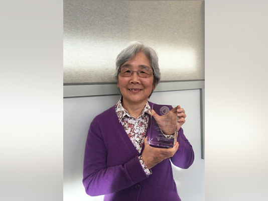A smiling woman holding a glass award.