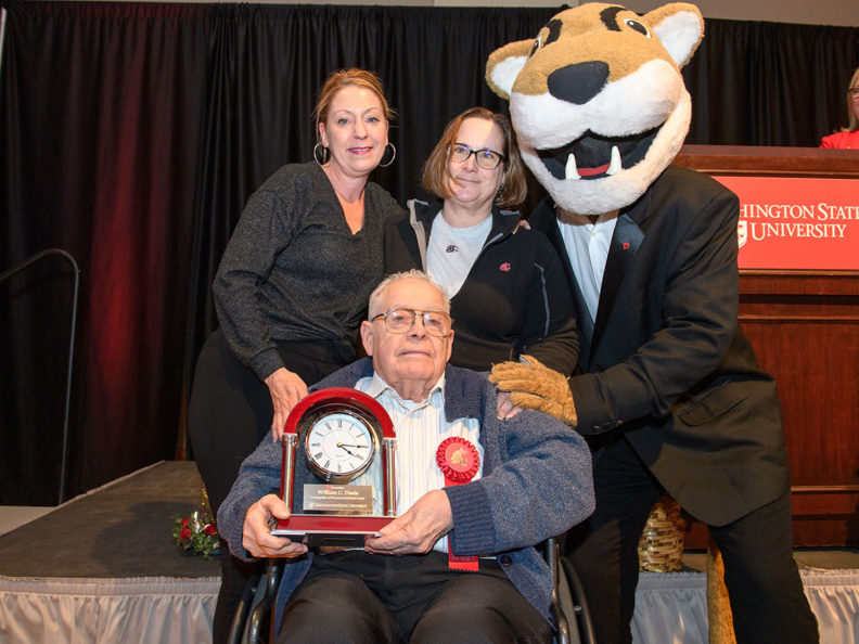 A seated man holding a clock award with two smiling women standing behind him next to a person wearing a WSU Cougar mascot costume and a suit.