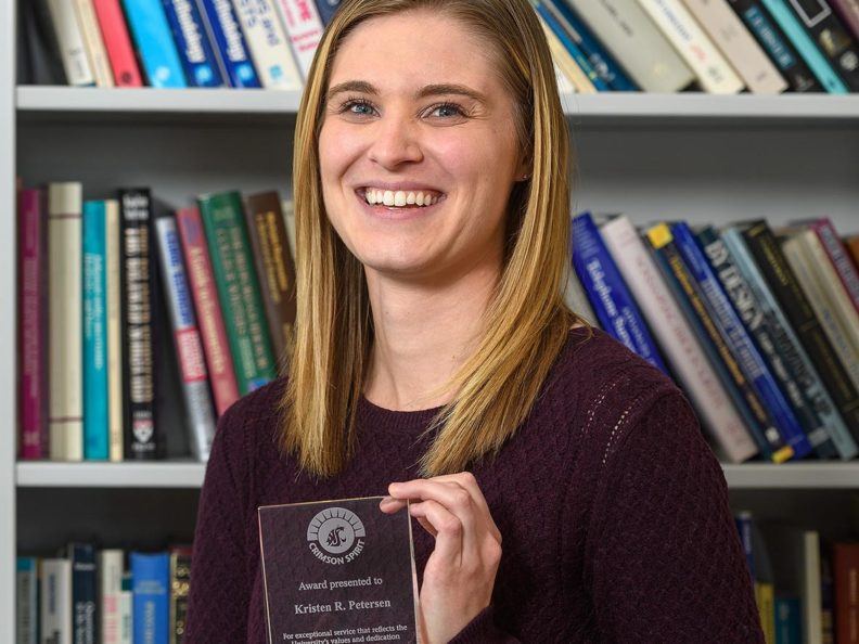 A smiling woman holding a glass award and standing in front of a bookshelf.