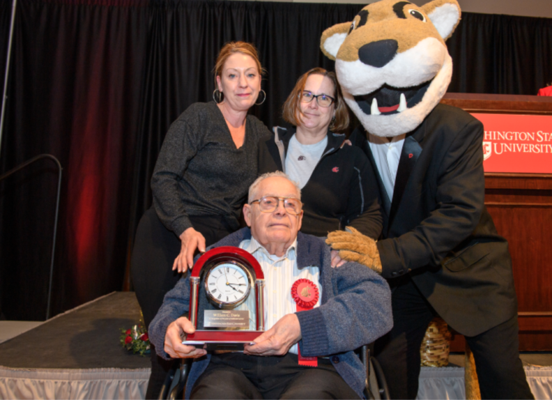 Man seated in chair holding glass award with two people and Butch Cougar mascot standing behind him.
