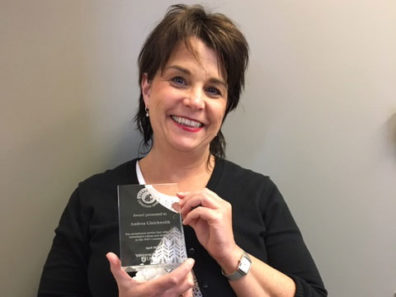 A smiling woman with short dark hair holding a glass award.