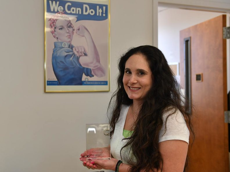 Smiling woman with long dark hair holding an award standing in front of a Rosie the Riveter poster.