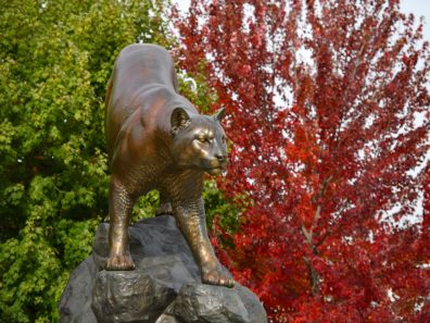 A statue of a cougar with green- and red-leaved trees.