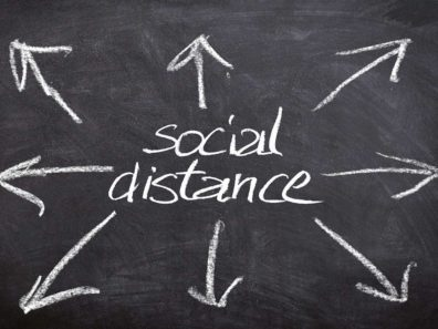 "A chalkboard with the words ""Social distance"" and arrows pointing away."