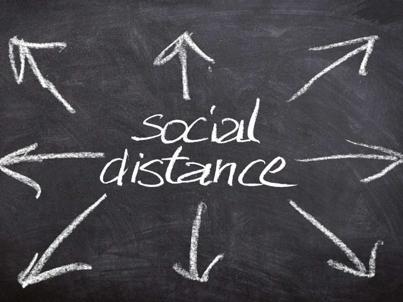 """A chalkboard with the words """"Social distance"""" and arrows pointing away."""