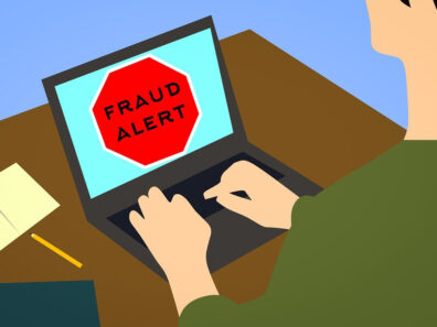Illustration of a person using a laptop that has a large red stop sign on it with the word fraud.