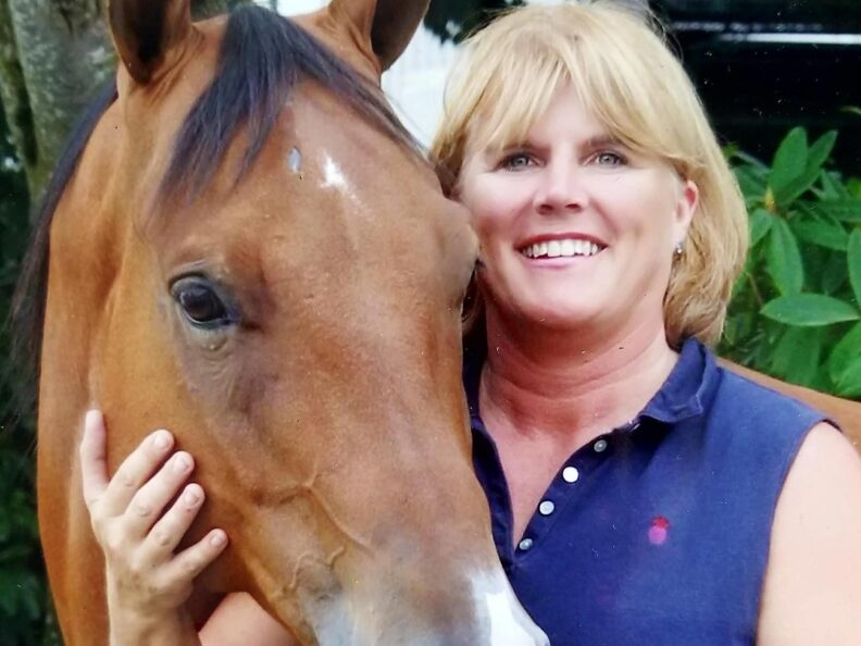 A smiling woman standing next to a horse.