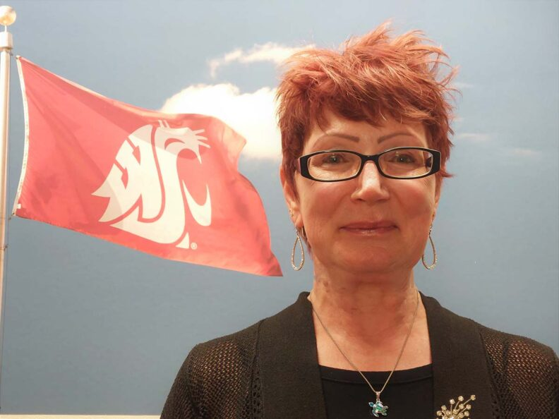 A smiling woman in front of a flag featuring the WSU cougar head.